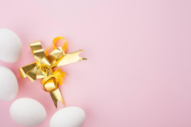 黄金の弓でピンクの背景に白い卵