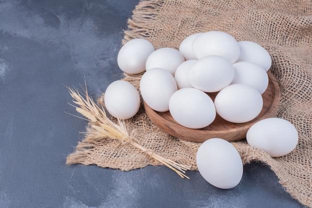 Белые яйца на куске мешковины.