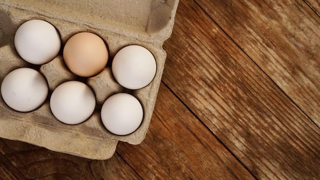 木製の背景に白い卵。イースターと健康食品の朝食料理のコンセプト