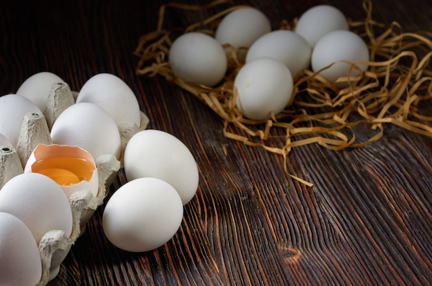 White eggs in a pack on paper straw and wooden table. broken egg with yolk on the front. low key.
