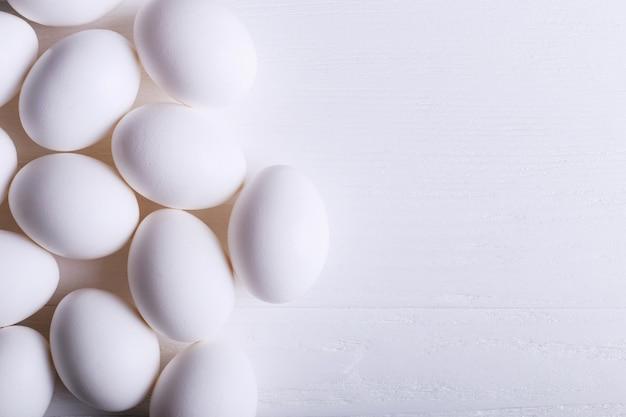 木製テーブルの上の白い卵パターン。