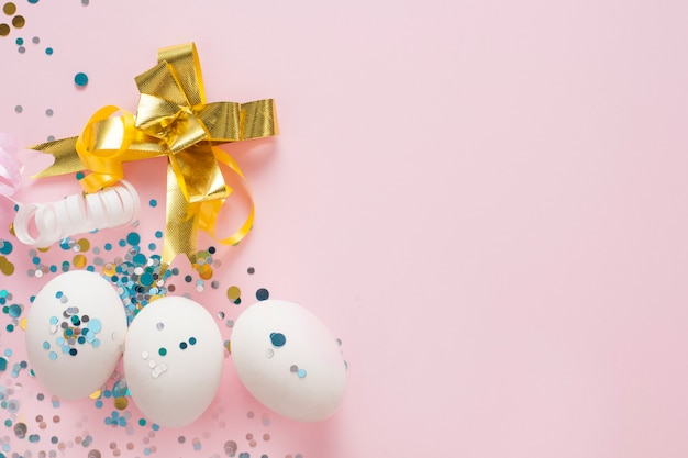 White eggs on a pink background, decorated with a gold bow, with copy space. easter concept.