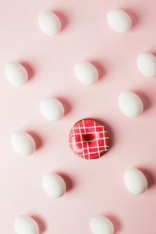 White eggs and pink donut on a light pink background with reflection of the shadows