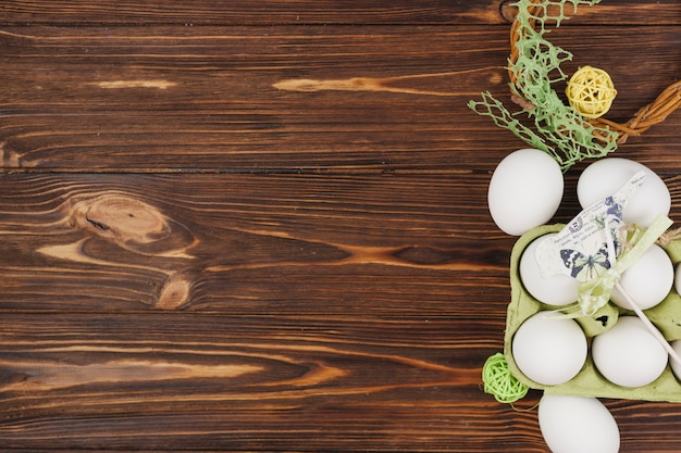 White eggs in rack with small bird on table