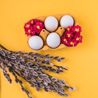 White eggs in rack with willow branches on table