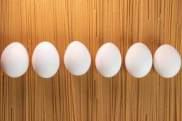 Uova bianche sulla pasta cruda