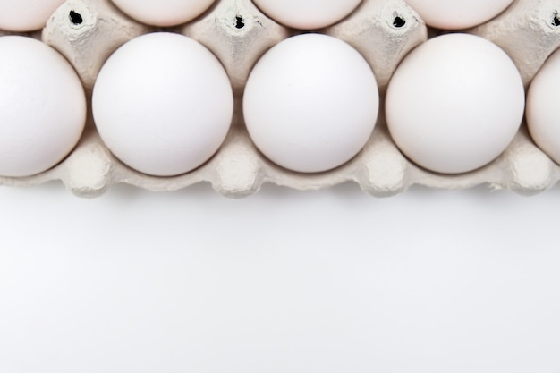 White eggs in recycled carton pressed box container on white table with copy space.
