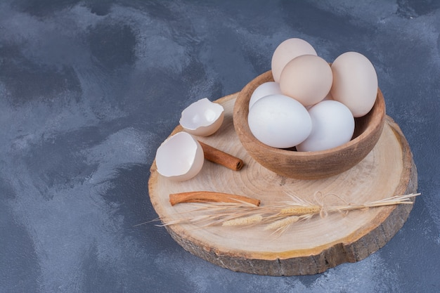 White eggs in a wooden cup on a wooden board