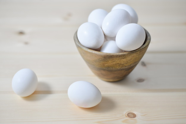 White eggs on wooden plate on wooden background , copy space