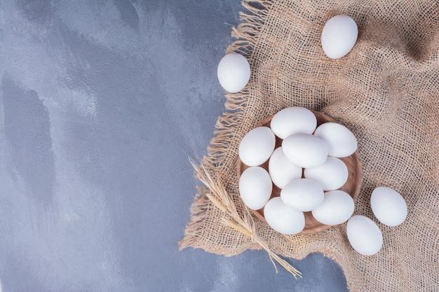 Uova bianche in un vassoio di legno sulla tela