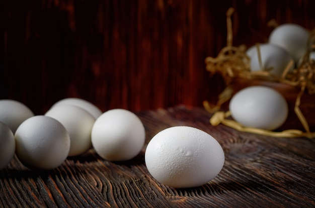 White eggs on a wooden table, eggs in a wooden bowl in the background. close up. low key.