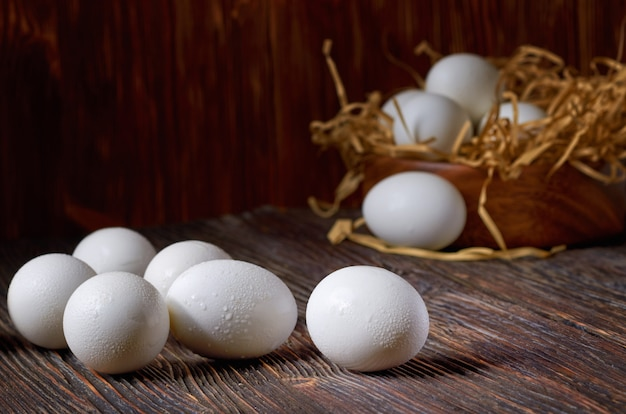 White eggs on a wooden table, eggs in a wooden bowl in the background. low key.