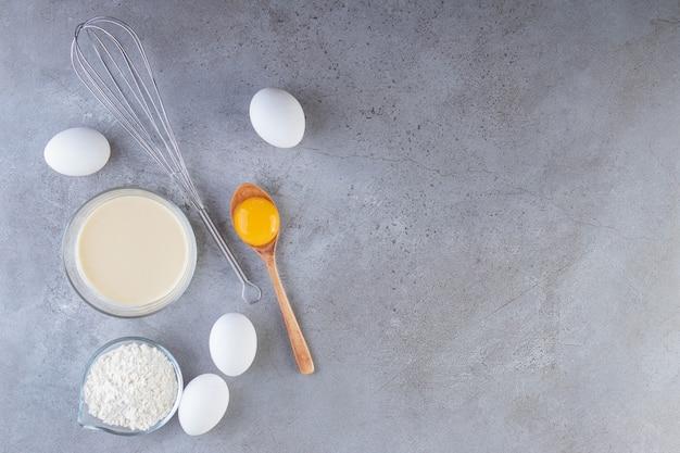 Uova bianche, tuorlo e ciotola di farina sul tavolo di pietra.