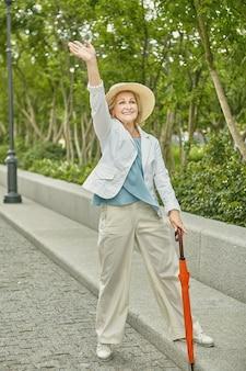 62 세 정도의 백인 노인 예쁜 아가씨가 공원의 포장 도로에 서서 여행을하고있다.