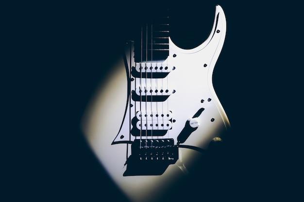 白いエレキギター。楽器のネックと指板。明るい影のクリエイティブなスタイル。