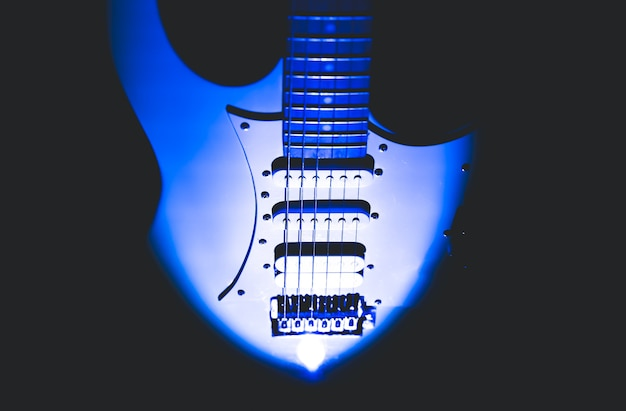 White electric guitar. neck and fingerboard of musical instrument. creative style with light shadows.