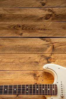 コピースペース付きの茶色の木製のテーブルに白いエレクトリックギター。