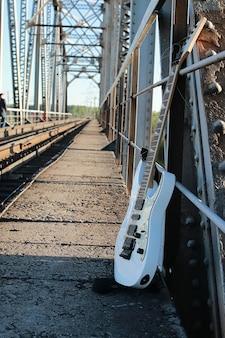 線路と工業用灰色の石の白いエレキギター