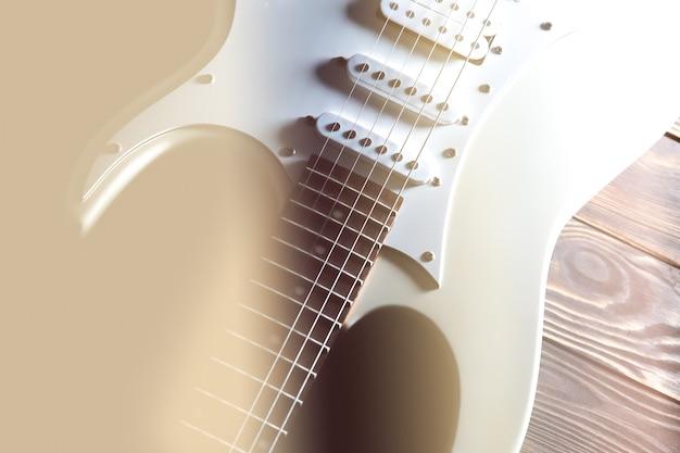 나무 배경에 흰색 일렉트릭 기타입니다. 음악 개념입니다. 밝은 그림자가 있는 창의적인 스타일.