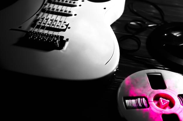 나무 배경에 흰색 일렉트릭 기타입니다. 오래된 릴투릴 테이프 레코더 카세트. 레트로 음악 개념입니다. 흑인과 백인 그림자입니다.