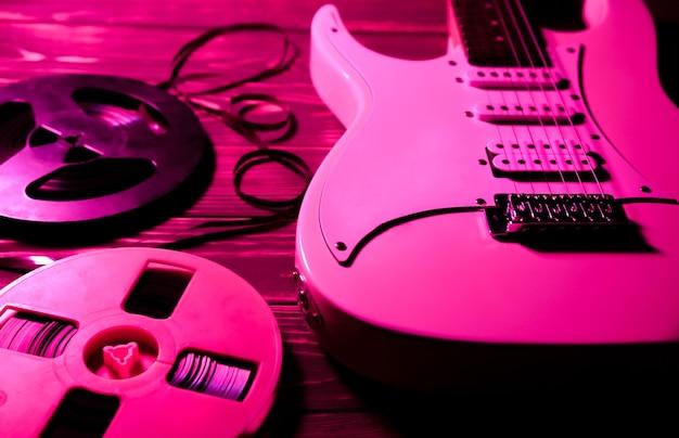 나무 배경에 흰색 일렉트릭 기타입니다. 오래된 릴투릴 테이프 레코더 카세트. 레트로 음악 개념입니다. 붉은 그림자.