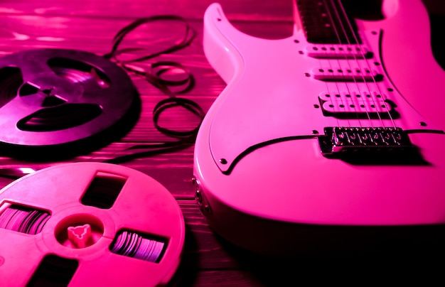 White electric guitar on wooden background. old reel-to-reel tape recorder cassettes. retro music concept. red shadows.