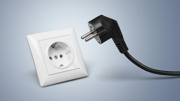 벽에 있는 전기 소켓에 있는 흰색 전기 플러그