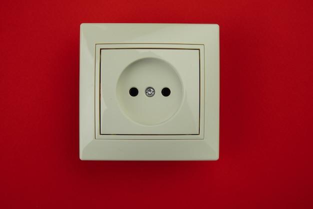 Белая электрическая розетка, изолированные на красном фоне