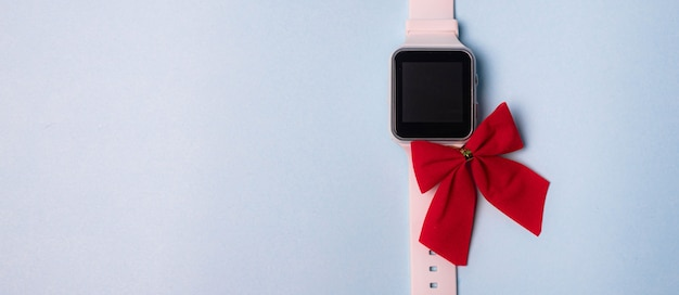 White electronic watch with a bow on a plain background