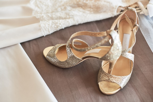 White elegant wedding dress and shoes lying on the bed.