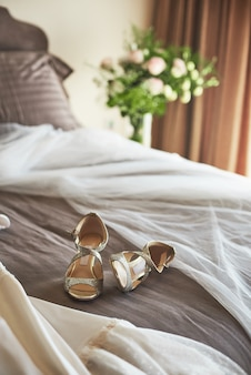 White elegant wedding dress, veil and shoes lying on the bed.