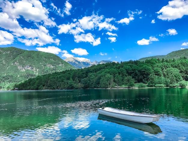 Белая пустая лодка посреди чистого горного озера блед в словении