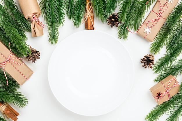 Белая пустая керамическая тарелка с копией пространства на белом столе с елочными украшениями из еловых отрубей ...
