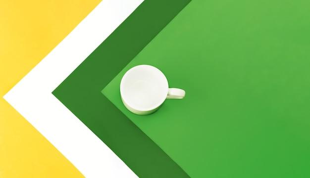 色とりどりのテーブルでコーヒーや紅茶の白い空のカップ