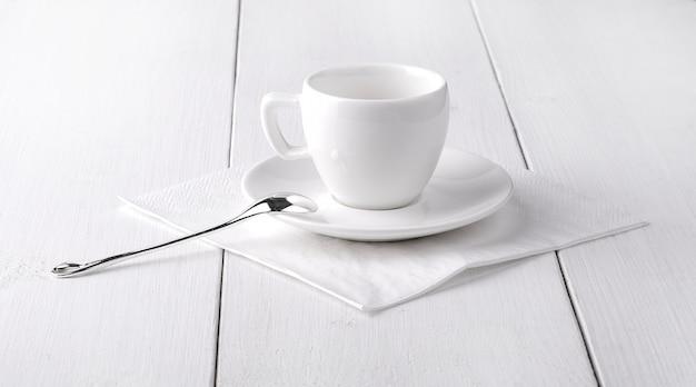 Белая пустая чашка кофе на белой салфетке.