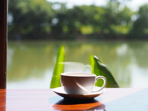 Белая пустая чашка кофе на деревянном столе рядом с стеклянным окном
