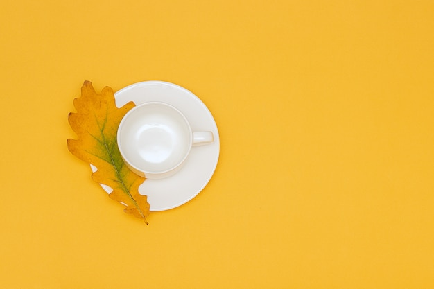 White empty cup with saucer and autumn oak leaf on yellow background.