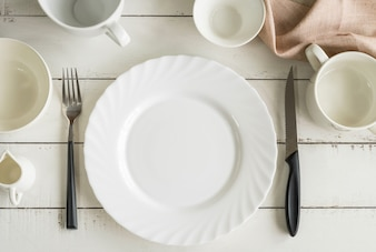 White empty dishes on wooden table with copy space