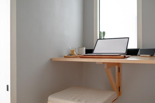 Белый пустой дисплей ноутбука на деревянном столе в квартире.