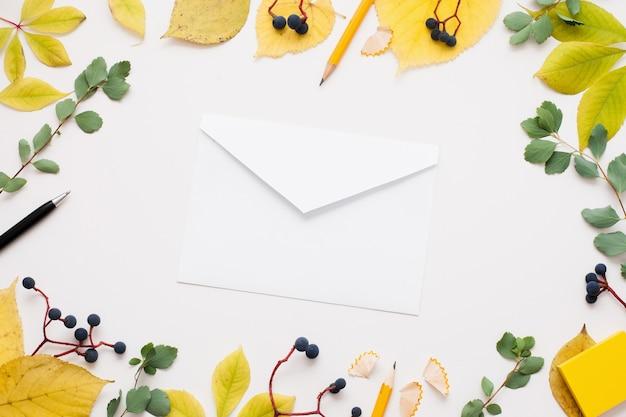 Белый пустой конверт в рамке из осенних листьев