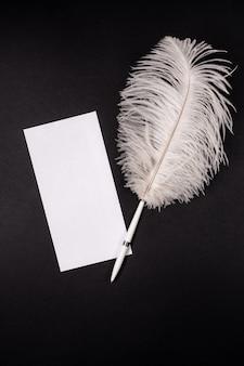 White empty envelope with retro feather pen on black
