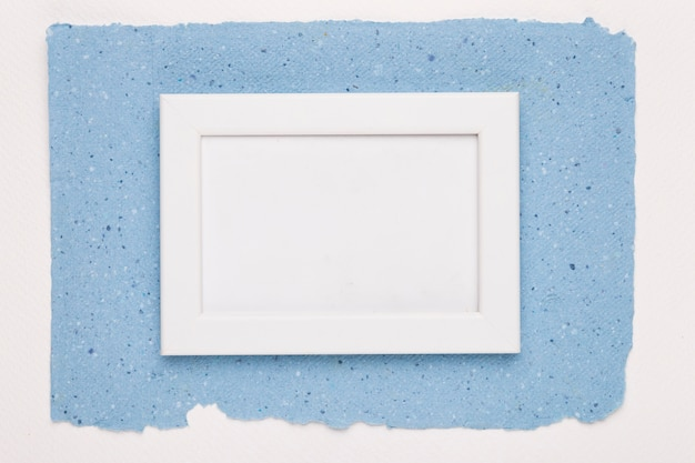 White empty frame on blue paper over white backdrop
