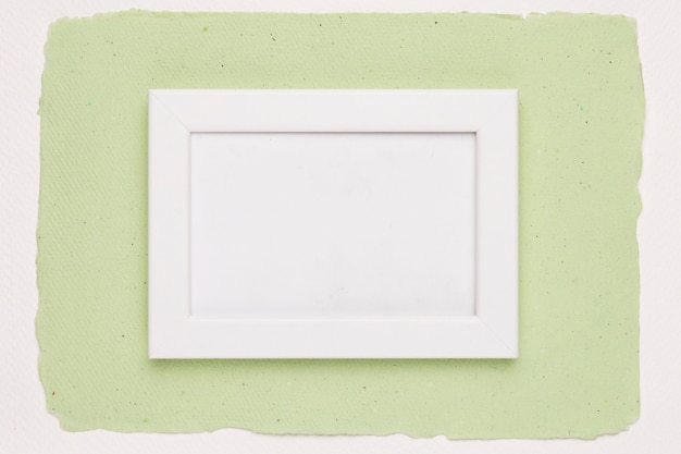 White empty frame on green paper background