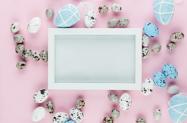 White empty frame with colored eggs around on pink