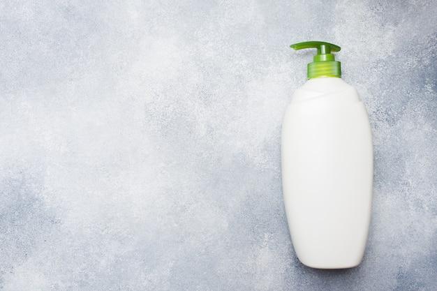 White empty liquid bottle on concrete background.
