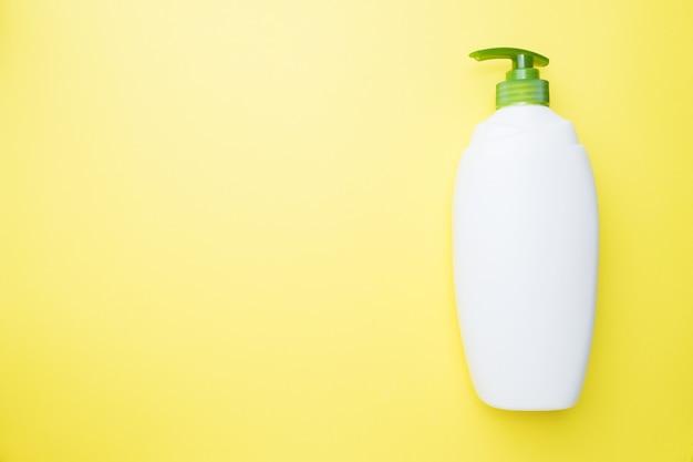 White empty liquid bottle on yellow background.