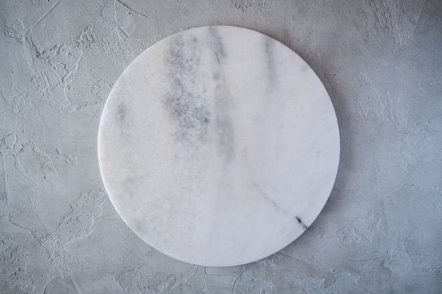 White empty marble texture round board on grey background. top view. copy space.