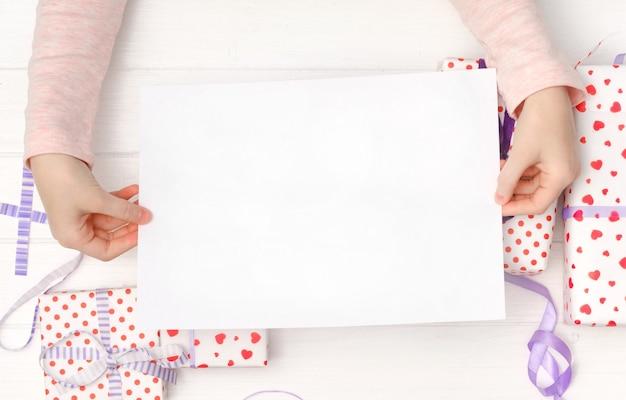 テーブルの休日のコンセプトに手と贈り物の白い空の紙 Premium写真