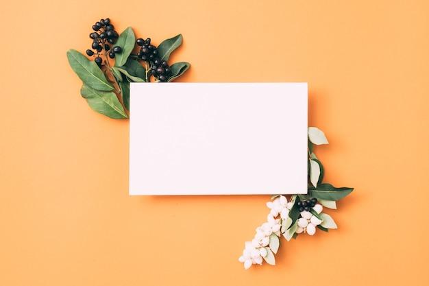 Белая пустая бумажная записка или карточка с декором ягод.