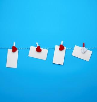 Белые пустые бумажные прямоугольные визитки на декоративных прищепках с красным сердечком